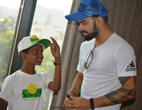 Virat Kohli sharing some batting tips with a Smile Foundation kid