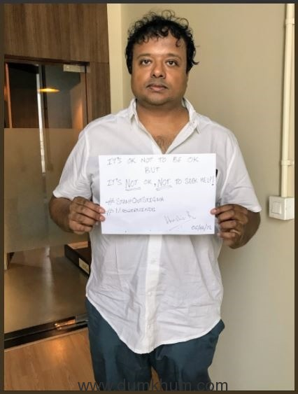 Hrishikesh Kannan holding up the Its ok not to be ok placard